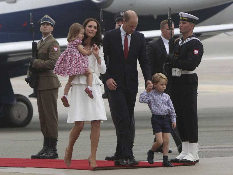 Britain's Kate, the Duchess of Cambridge holds Princess Charlotte as they arrive at the airport, in Warsaw , Poland, Monday, July 17, 2017.