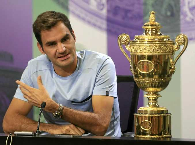 Switzerland's Roger Federer speaks to the media with the Wimbledon trophy.