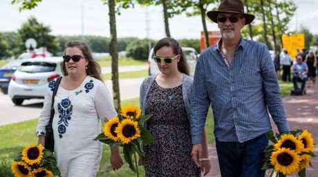Relatives of MH17 victims flowers as they arrive at a service to mark the three-year anniversary of the downing of the plane.