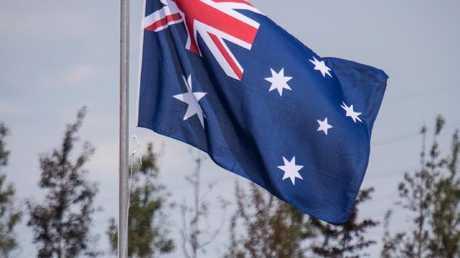 An Australian flag flies at half-mast at the memorial.