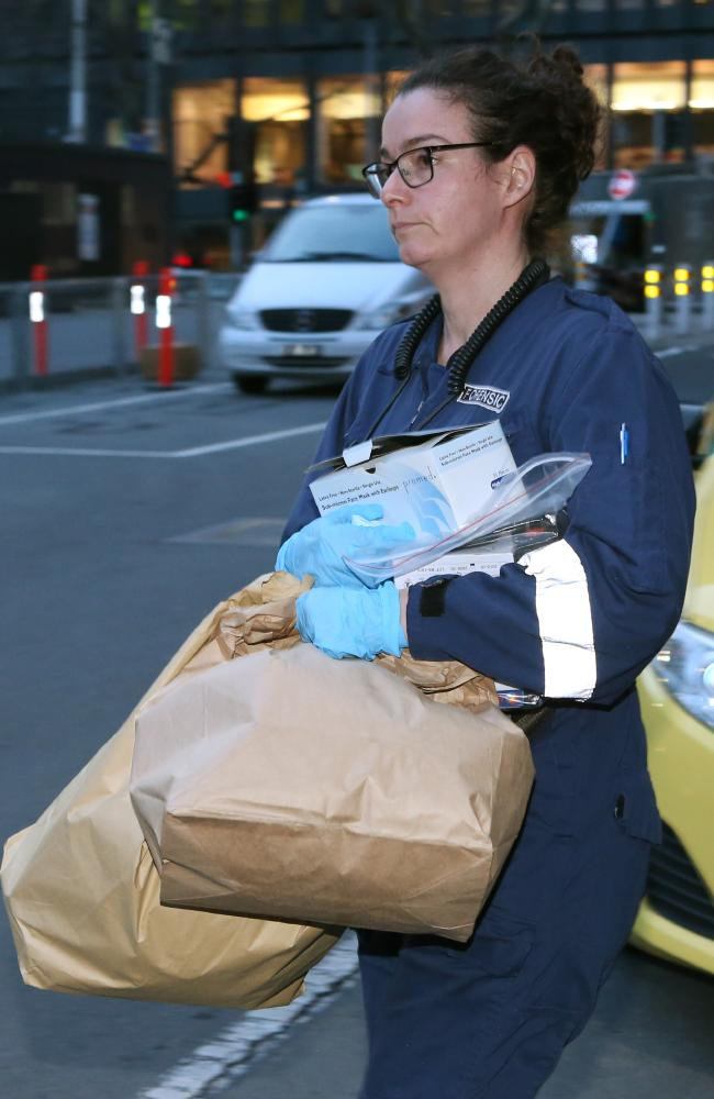 A forensic officer leaves Oaks on Market with evidence. Picture: David Crosling