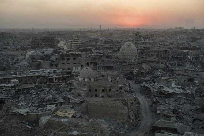The sun sets behind destroyed buildings in the west side of Mosul, Iraq.  (AP Photo/Felipe Dana)
