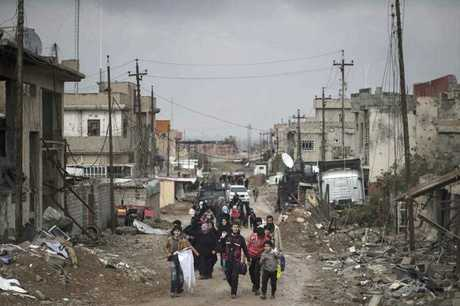 Iraqi civilians flee their homes during fighting between Iraqi security forces and Islamic State militants, on the western side of Mosul, Iraq.
