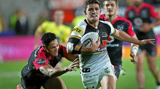 Nathan Cleary of the Panthers beats the tackle of Roger Tuivasa-Sheck of the Warriors.