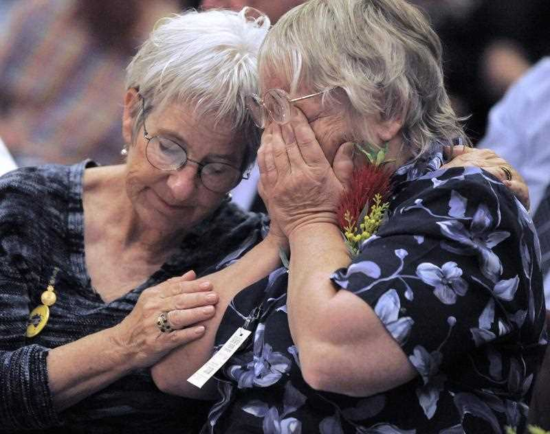 Two women comfort each other as they attend a 2009 ceremony where Australian Prime Minister Kevin Rudd issued an apology to thousands of impoverished British children shipped to Australia with the promise of a better life, only to suffer abuse and neglect thousands of miles from home.