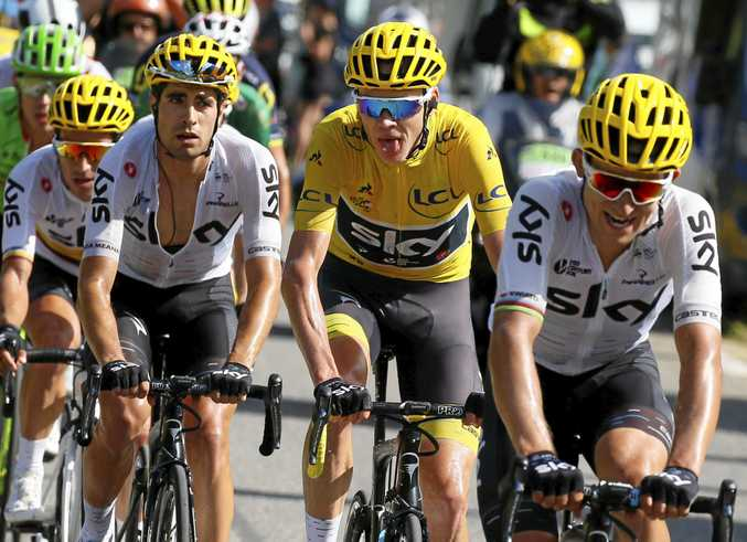 Britain's Chris Froome, wearing the overall leader's yellow jersey, grimaces as he rides with teammates Poland's Michal Kwiatkowski, right, and Spain's Mikel Landa, left
