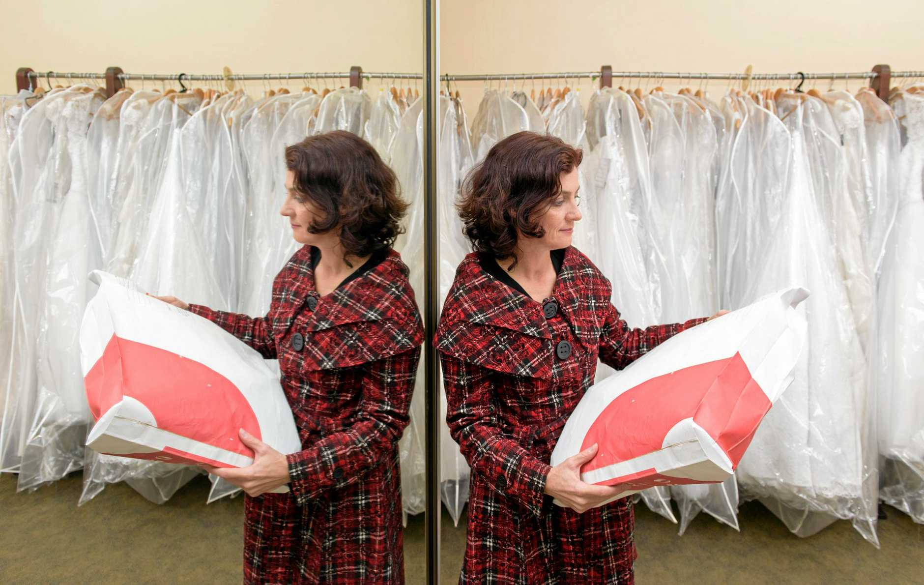 Leah Stevenson of Lasting Impressions Bridal Wear with a package she is about to send to a bridal shop in Canberra after the collapse of bridal manufacturer Alfred Angelo.