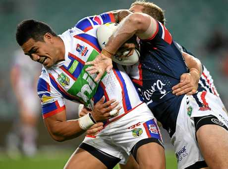 Peter Matautia of the Knights is tackled by Mitchell Aubusson of the Roosters.