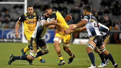 Ardie Savea of the Hurricanes is tackled by the Brumbies defence.