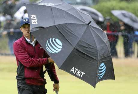 Jordan Spieth of the United States shelters from the rain as he walks along the 18th fairway.