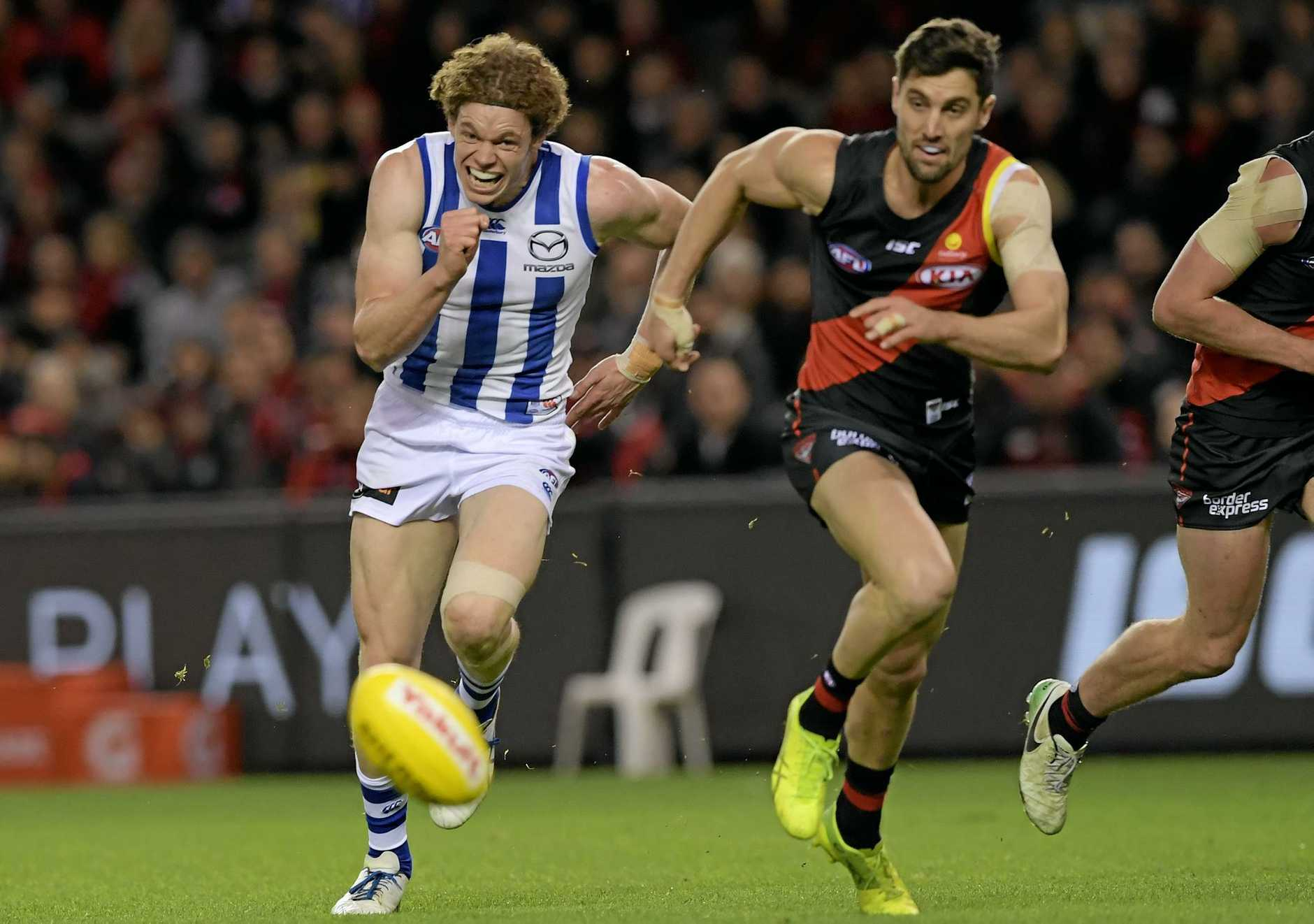Ben Brown of the Kangaroos (left) runs for the ball with David Myers of the Bombers.