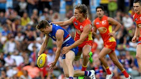 Lachie Hunter of the Bulldogs is tackled by Darcy Macpherson of the Suns.