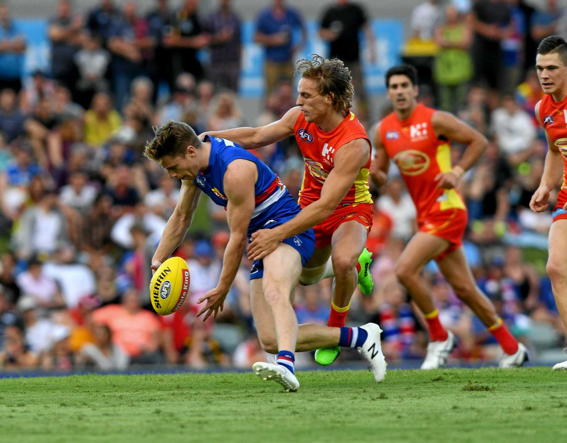 Lachie Hunter of the Bulldogs is tackled by Darcy McPherson of the Suns during the Round 18 AFL match between the Western Bulldogs and the Gold Coast Suns at Cazaly's Stadium in Cairns, Saturday, July 22, 2017. (AAP Image/Brian Cassey) NO ARCHIVING, EDITORIAL USE ONLY
