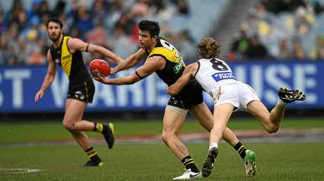 Tigers midfielder Trent Cotchin (centre) gets the ball away despite the attentions of Giants rival Callan Ward.