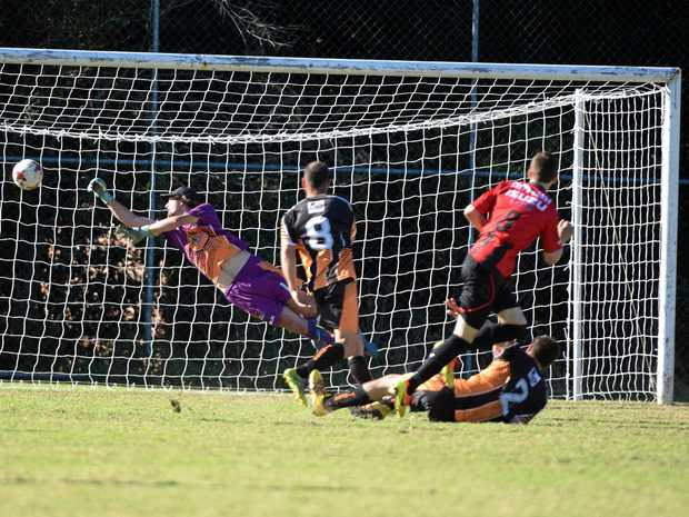 GOAAALLL: Nick Mallett scores a great goal for the Coffs United Lions past the desperate dive of Coffs Coast Tigers goalkeeper Jake Tarrant.