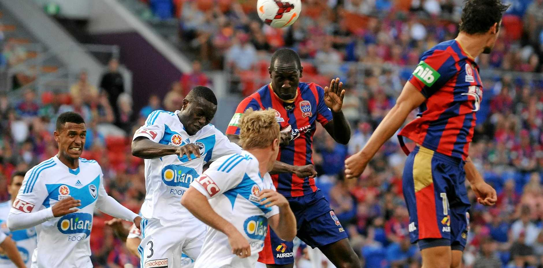 TARGET MAN: Newcastle Jets striker Emile Heskey heads the ball his side's match against Melbourne Victory. The ex-Liverpool man believes boosting the salary cap will help improve the future of the A-League.