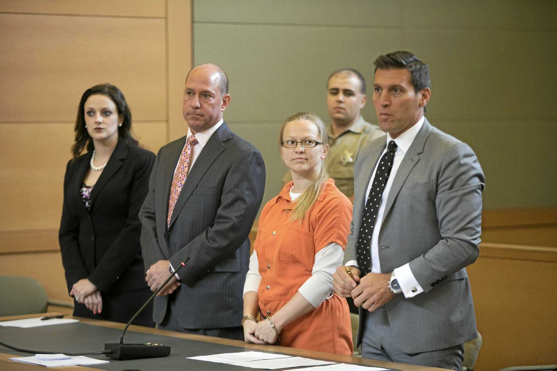 Accompanied by her attorneys, Angelika Graswald, second from right, stands in an Orange County court.