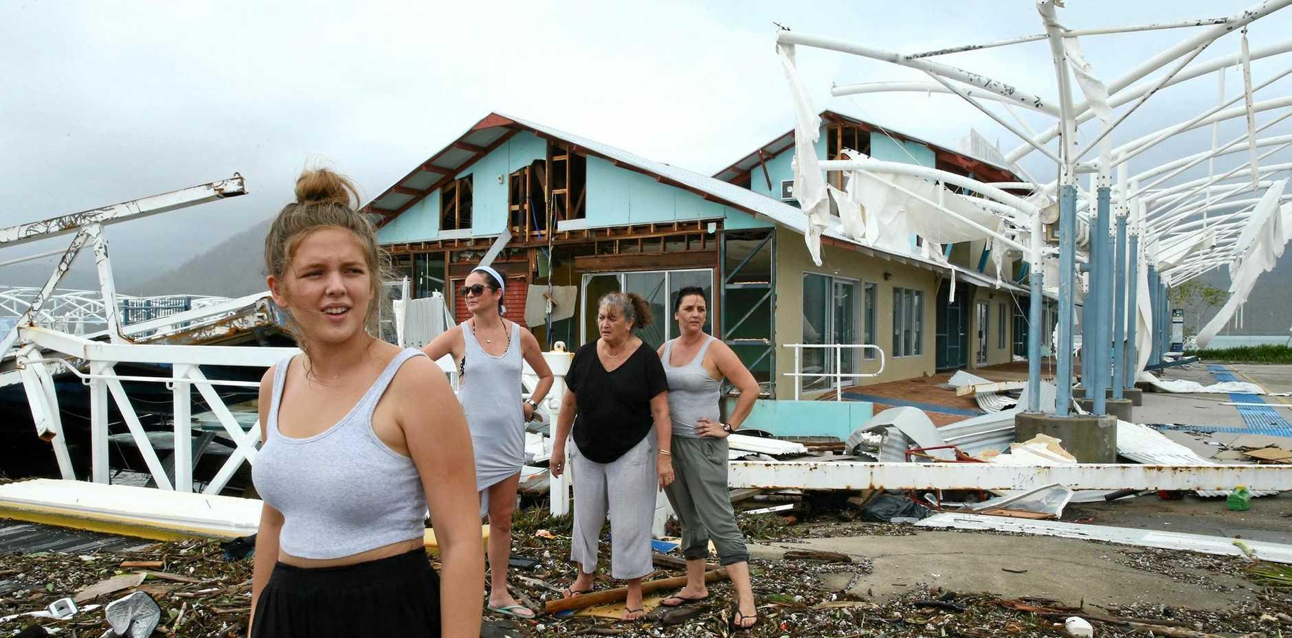 Airlie Beach residents Maika McDonald,15, Lauren Squires, Karen Gordon and Katelin Gordon survey the damage at Shute Harbour after Cyclone Debbie.