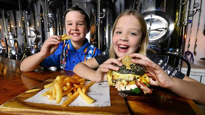 FAST FLAVOUR: Adrian Butler, 10, and sister Alyssa Butler, 9, of Bellbird Park enjoy the new Hot Lap burger at the Pumpyard Bar and Brewery.