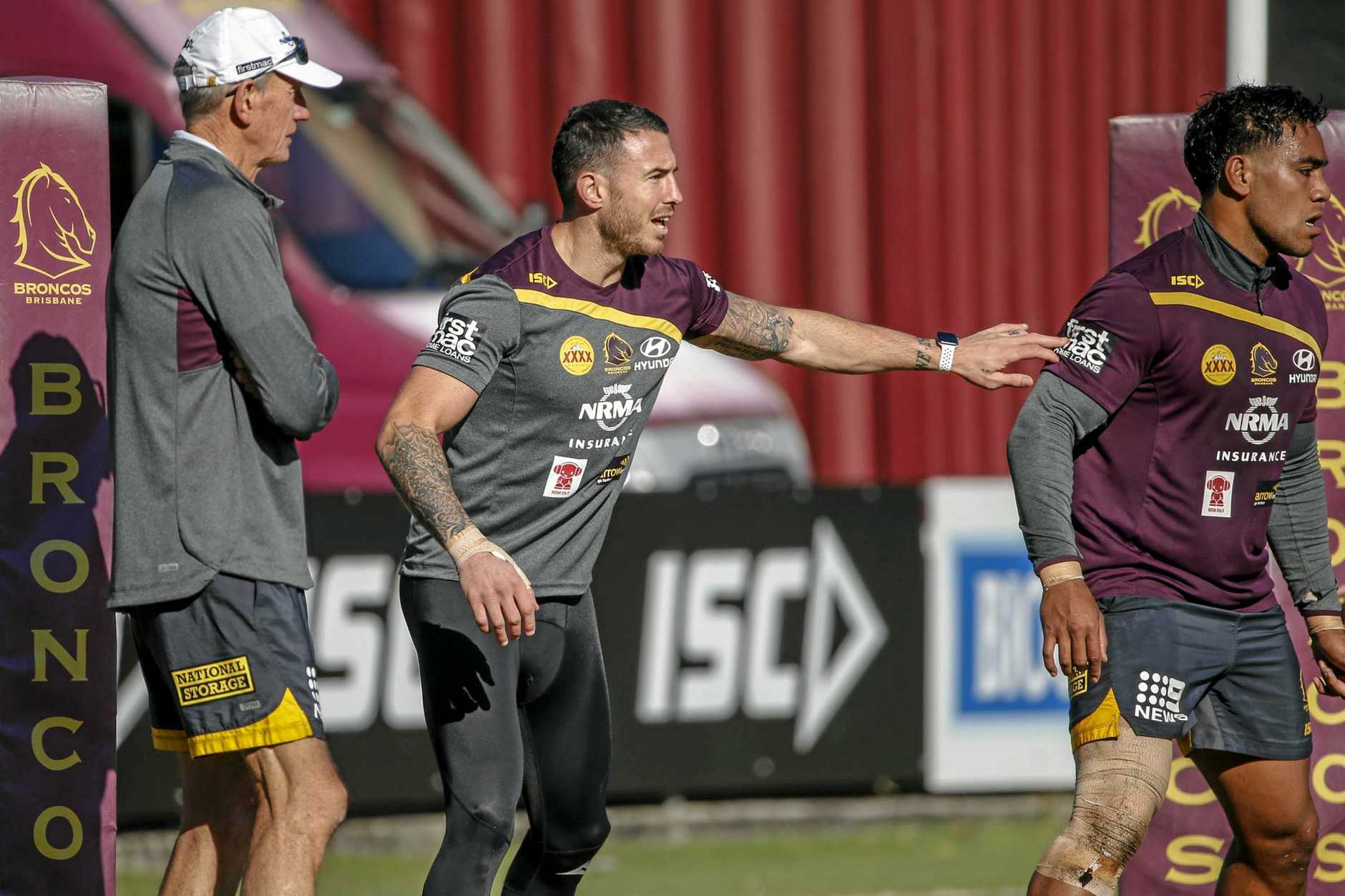 Darius Boyd (centre) barks orders at a Broncos training session as coach Wayne Bennett (left) watches on.