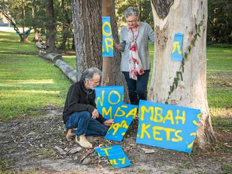 Jim McIndoe and Nerida Dufficy stand with one of the damaged Woombah market signs.