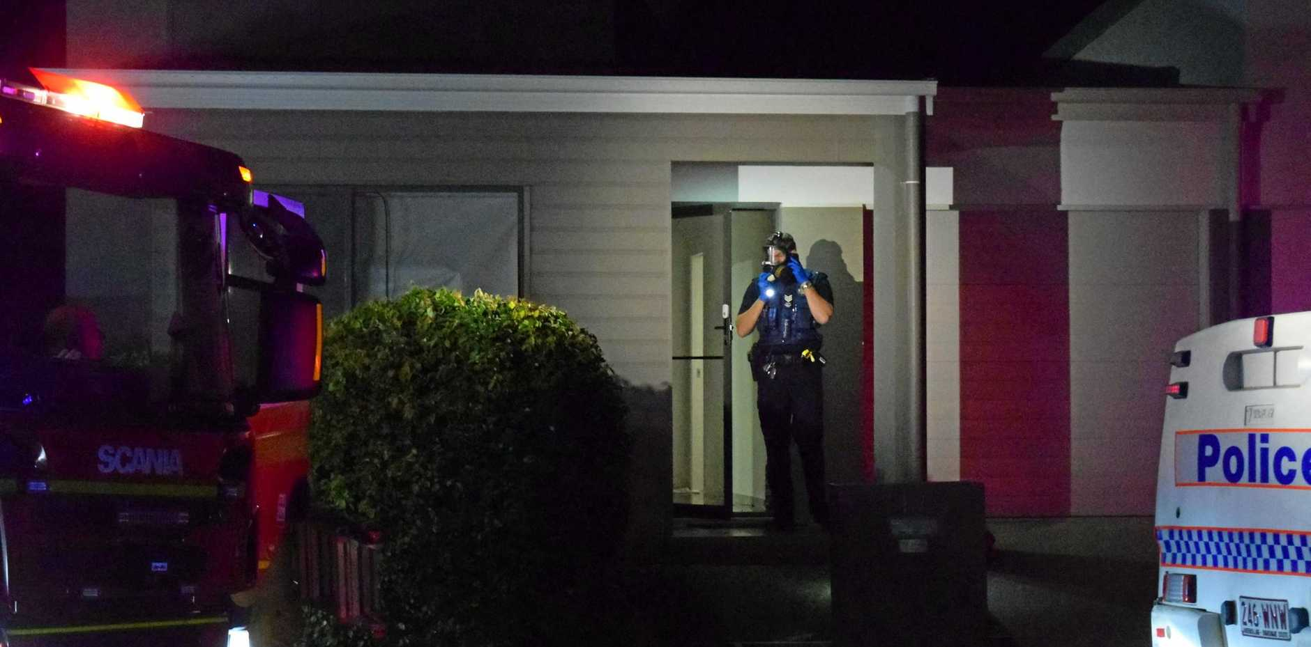 MASKED UP: A police officer in a gas mask prepares to enter the house.