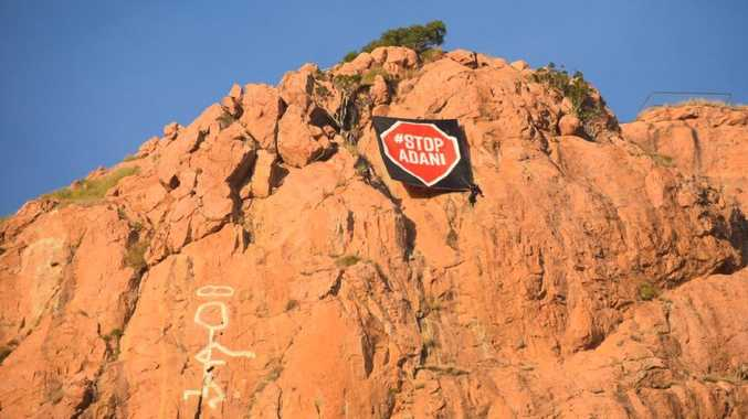 A banner unfurled on the heritage-listed Castle Hill by anti-Adani protesters. Photo: Twitter / Front Line Action Coal