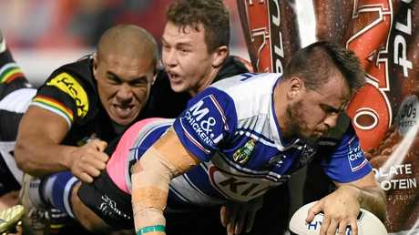 Josh Reynolds of the Bulldogs powers through the Panthers defence to score a try.