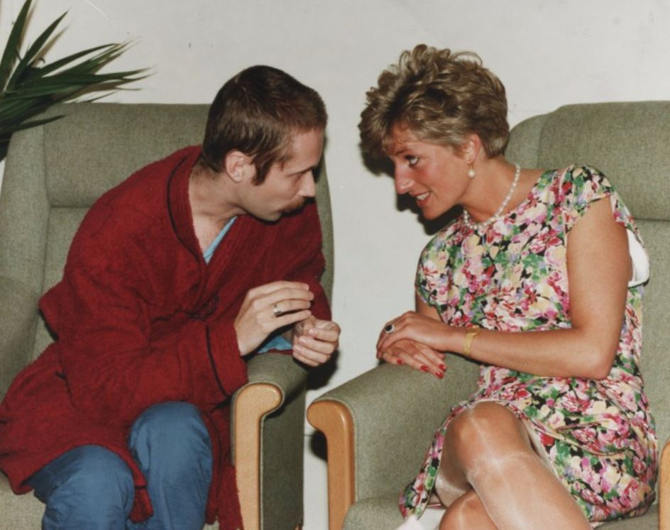 Princess Diana sits in a chair chatting with Steve, 28, at a centre for AIDS / HIV+ patients Middlesex Hospital London.