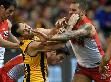 Luke Hodge of the Hawks (centre) and Lance Franklin of the Swans clash.