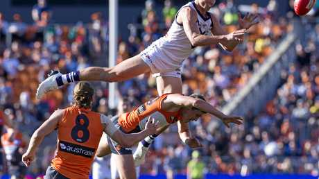 Ethan Hughes of the Dockers goes over the top of Harry Perryman of the Giants but fails to take the mark.