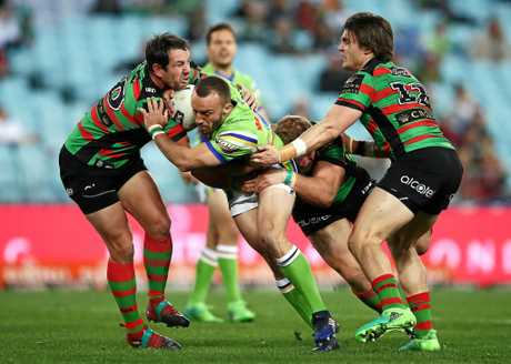 Josh Hodgson of the Raiders is tackled by the Rabbitohs defence.