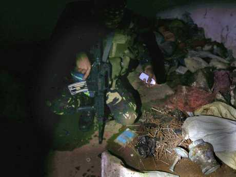 Soldiers from the 1st Field Artillery Battalion looking at what ISIS soldiers left behind in Marawi. Picture: Gary RamageSource:News Corp Australia