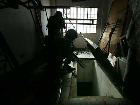 Soldiers from the 1st Field Artillery Battalion at a fire support base, outside of Marawi, inspect a cellar of an abandoned house where ISIS militants used to hide. Picture: Gary RamageSource:News Corp Australia