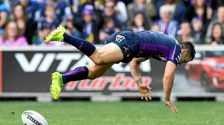 Storm halfback Cooper Cronk dives after scoring a try against Manly.