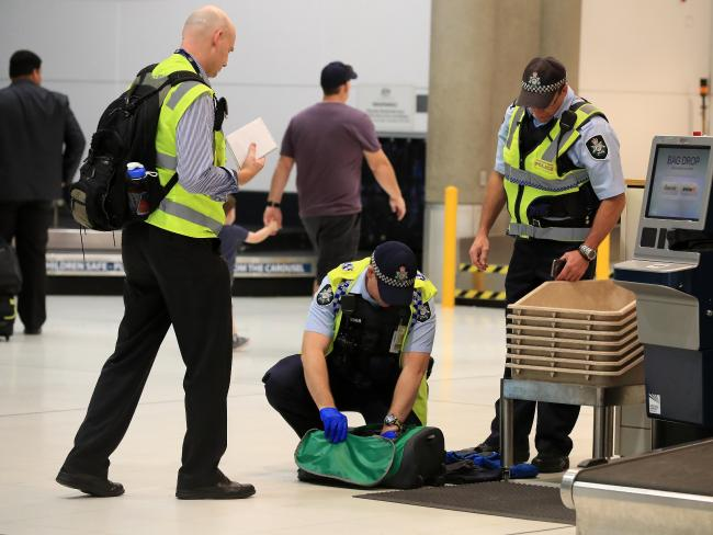 Security at Brisbane Airport has also been increased after a foiled terror plot in Sydney. A police officer goes through a bag. Picture: Adam Head