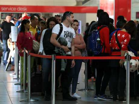 Security at Brisbane Airport has also been increased after a foiled terror plot in Sydney. Passengers queue to get through security on Sunday.