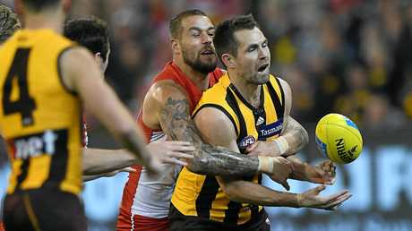 Luke Hodge the Hawks is tackled by Lance Franklin of the Swans.