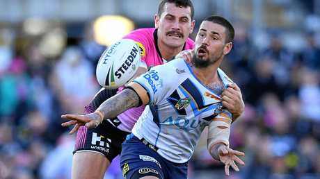 Nathan Peats of the Titans offloads a pass as he is tackled by Reagen Campbell-Gillard of the Panthers.