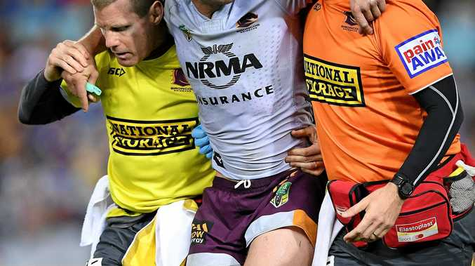 Andrew McCullough of the Broncos is assisted from the field by trainers after sustaining an injury against the Eels.