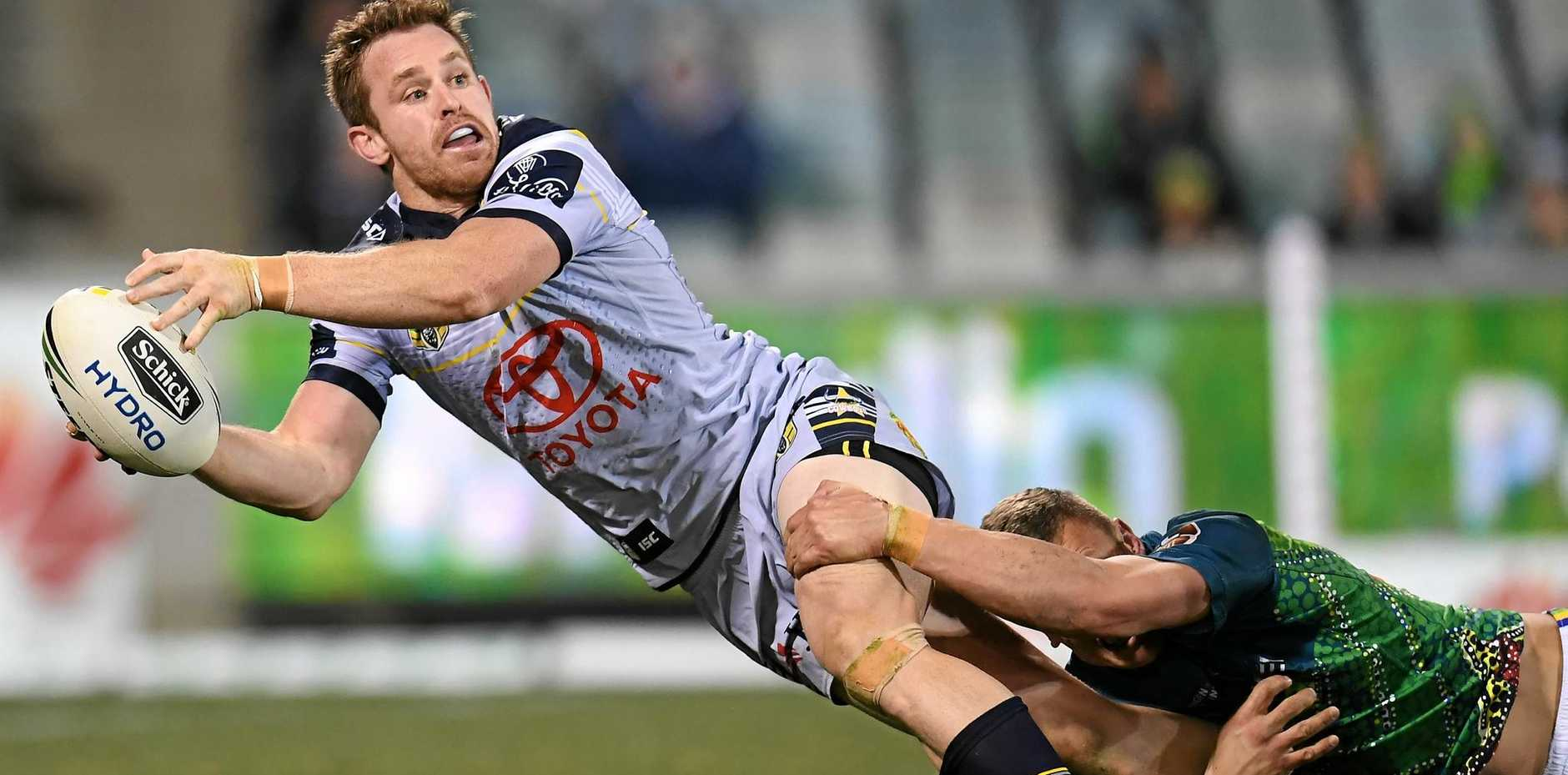 Michael Morgan of the Cowboys offloads to Te Maire Martin, who went on to score, as Jack Wighton of the Raiders tries to hold on.