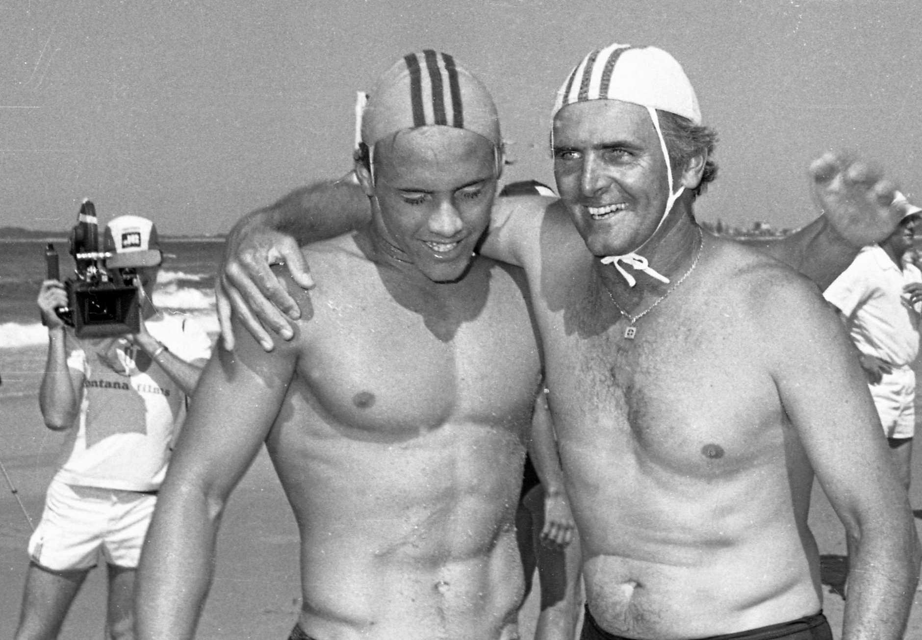 Ironman Grant Kenny wins Australian Senior and Junior ironman titles at Maroochydore Beach, 1980 and is congratulated by his dad Hayden Kenny.