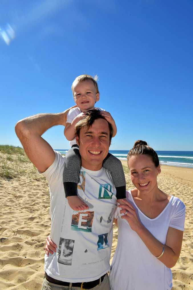 GROWING UP: Tom and Gemma Cox enjoy a walk on Warana Beach with their son William.