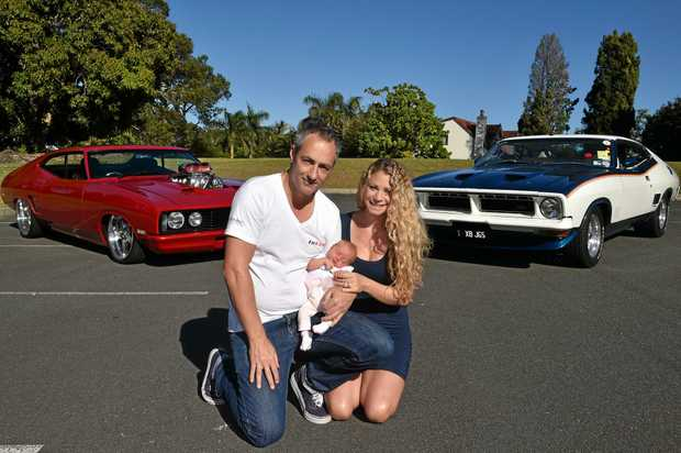 Brock and Claire Mahoney with their newborn Kaia and their prized Ford Falcon hardtops, a 1977 XC GS (left) and a 1975 Ford XB Falcon Hardtop John Goss Special.