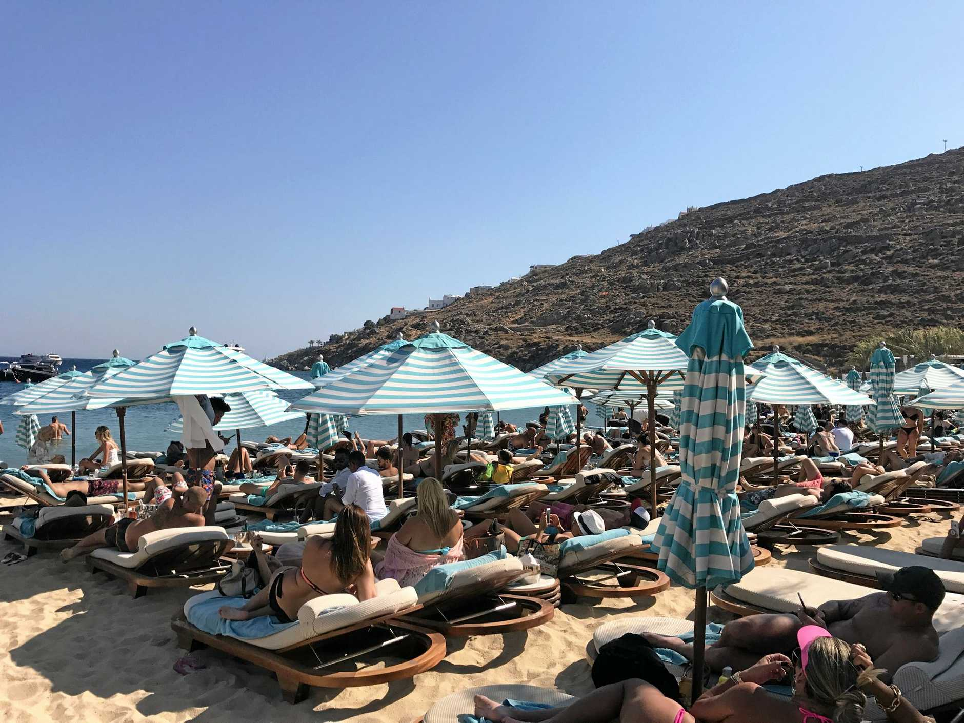 Tourists battle for space on the beach at Psarou Bay on Mykonos.