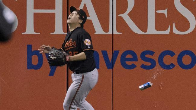 The moment: The beer can flies past Baltimore Orioles' Hyun Soo Kim on October 4, 2016. Picture: Mark Blinch/The Canadian Press via AP