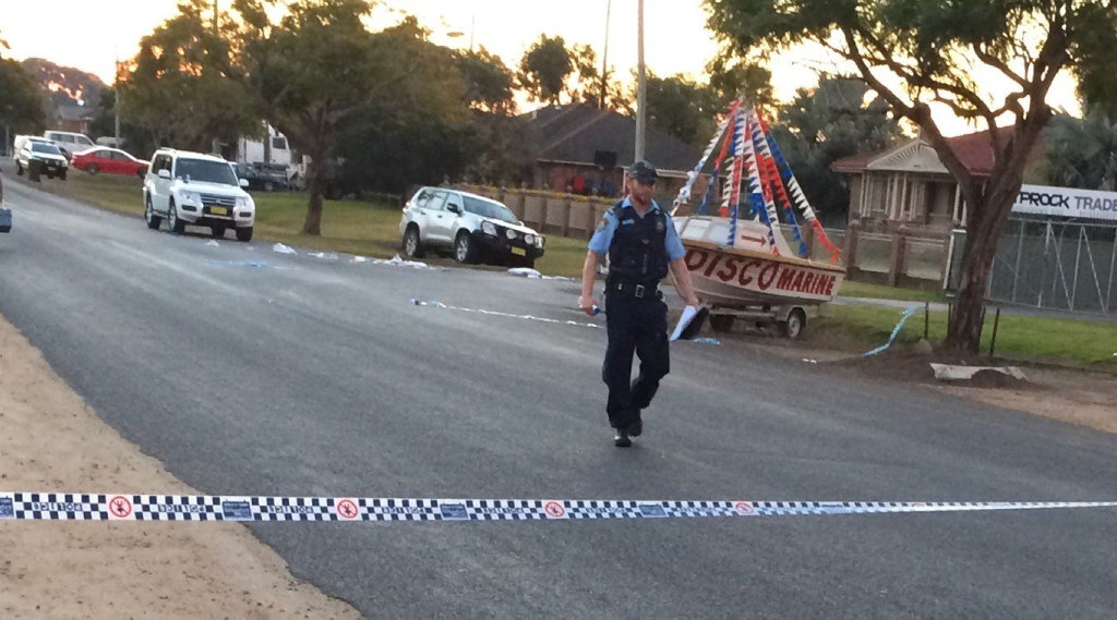 A police officer walks past the scene of a police shooting in North St, Grafton.