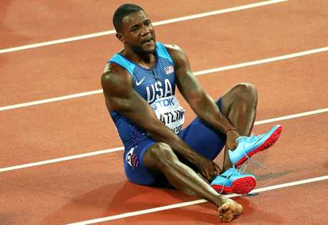 Gatlin takes off his shoes after victory.