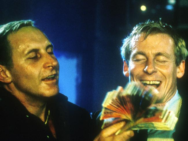 Rogerson, played by Roxburgh, and Neddy Smith (Tony Martin) in a famous scene from the first Blue Murder in which crook and cop enjoy the spoils of crime.