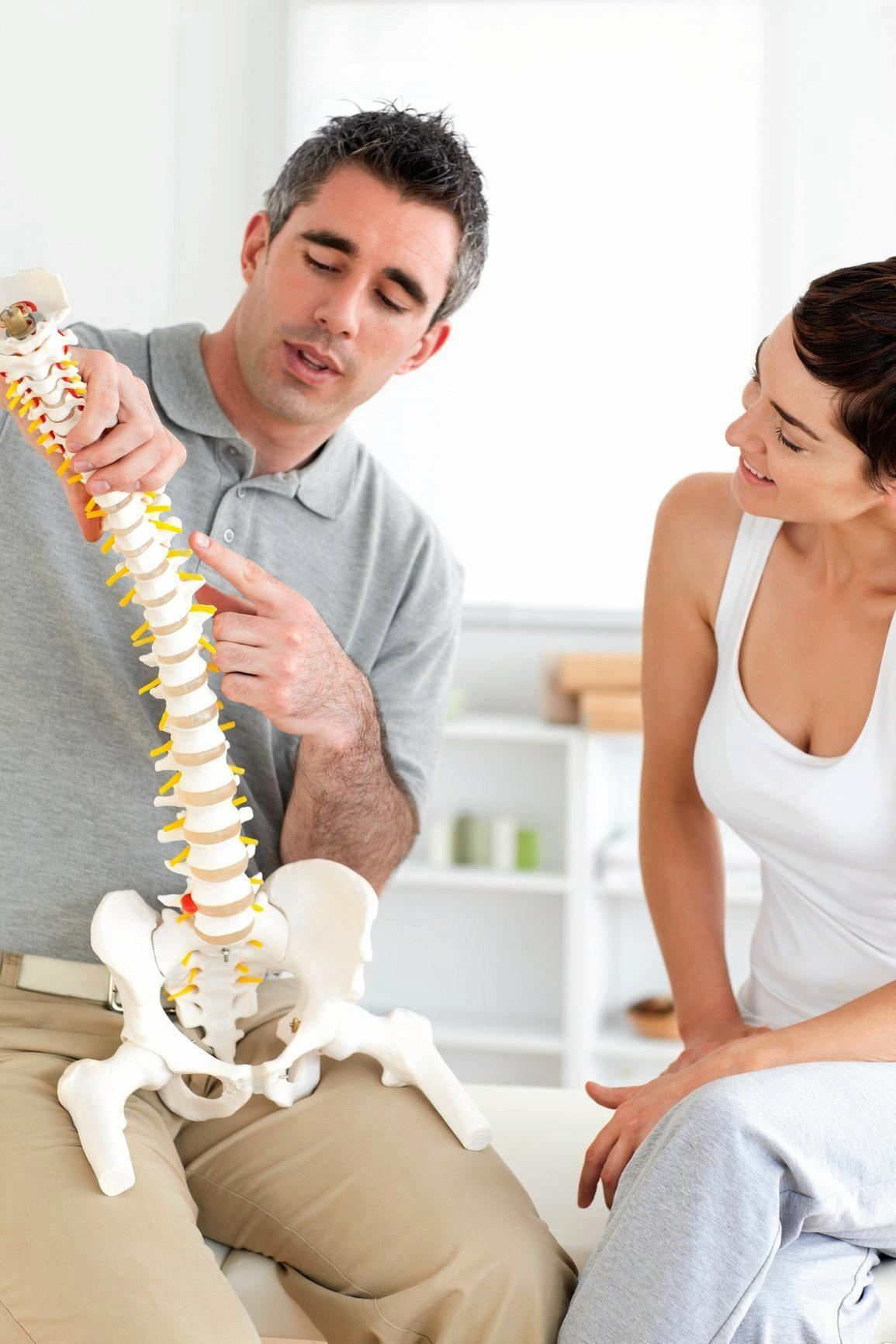 Chiropractor explaining the spine to a woman in a room